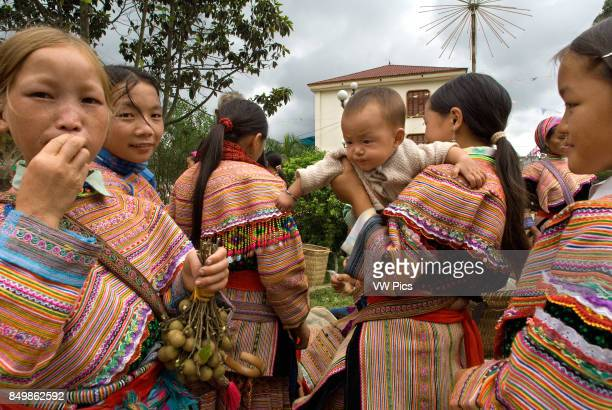 Bac Ha market Flower Hmong people in traditional dress at weekly market Sapa Vietnam Young women from the Flower Hmong minority ethnic group at the...