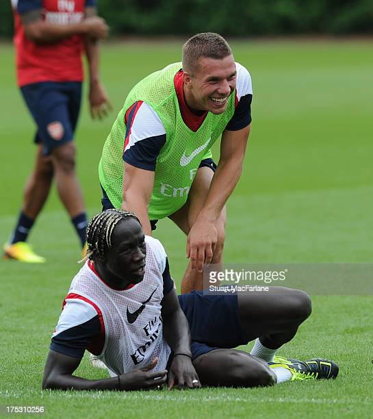 Bacary Sagna and Lukas Podolski of Arsenal joke around during a training session at London Colney on August 02 2013 in St Albans England