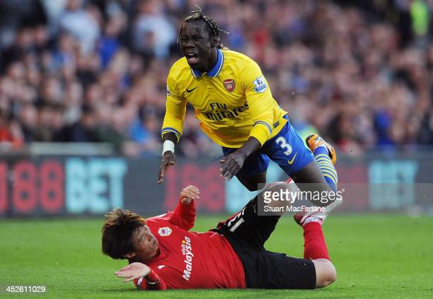 Bacary Sagna of Arsenal is fouled by BoKyung Kim of Cardiff at Cardiff City Stadium on November 30 2013 in Cardiff Wales