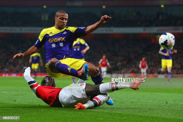 Bacary Sagna of Arsenal tackles Wayne Routledge of Swansea City during the Barclays Premier League match between Arsenal and Swansea City at Emirates...