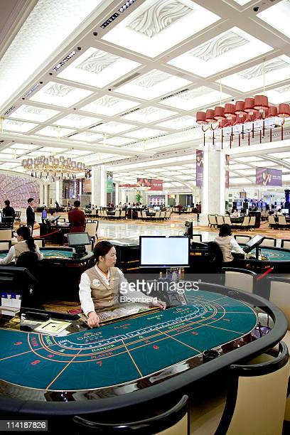 A baccarat dealer sits at her table on the opening day of Galaxy Entertainment Group Ltd newest casino resort in Macau China on Sunday May 15 2011...