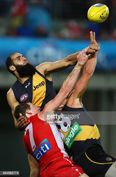 Bachar Houli and Alex Rance of the Tigers and Harry Cunningham of the Swans compete for the ball during the round 23 AFL match between the Sydney...