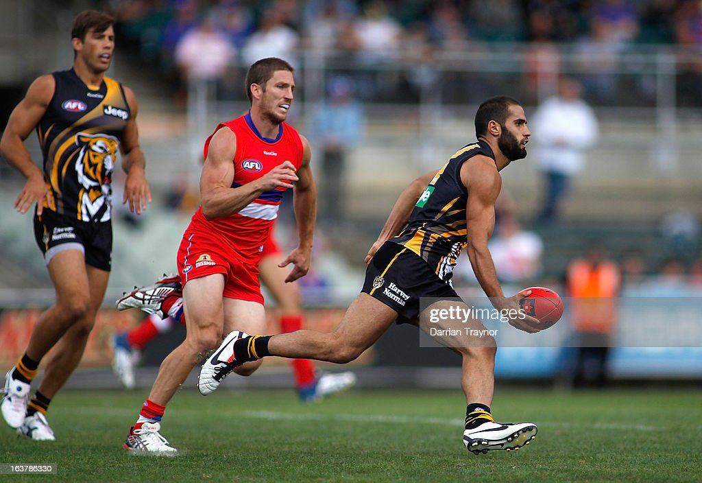 Bachar Houli of the Tigers handballs the ball during the AFL practice match between the Richmond Tigers and the Western Bulldogs at Visy Park on March 16, 2013 in Melbourne, Australia.