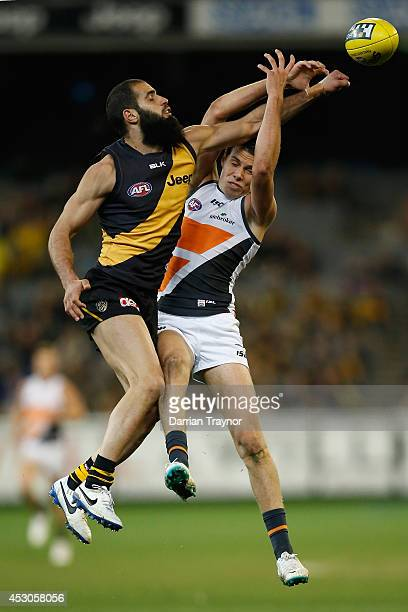 Bachar Houli of the Tigers punches the ball clear of Joshua Kelly of the Giants during the round 19 AFL match between the Richmond Tigers and the...