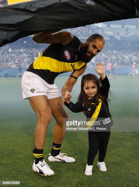 Bachar Houli of the Tigers runs through the banner with his daughter for his 150th match during the 2017 AFL round 01 match between the Carlton Blues...