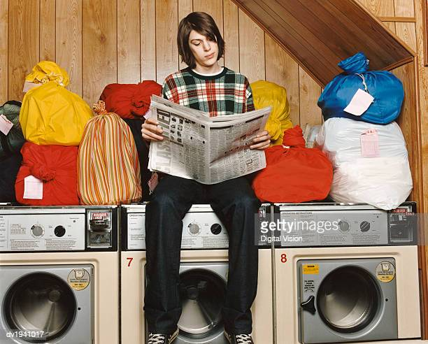 Bachelor Sitting On Top of a Washing Machine and Reading a Newspaper in a Launderette