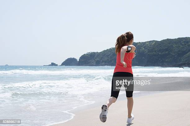 Back figure of a woman running on beach for diet