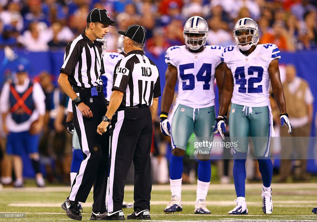 Back judge Larry Babcock talks with referee Jim Core during the 2012 NFL season opener between the New York Giants and the Dallas Cowboys at MetLife Stadium on September 5, 2012 in East Rutherford, New Jersey.