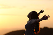 Back light of a woman breathing raising arms with a warm background