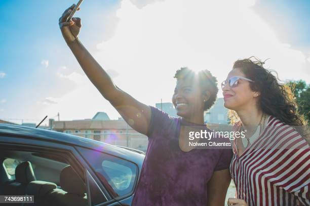 Back lit happy young woman taking selfie with female friend by car against sky
