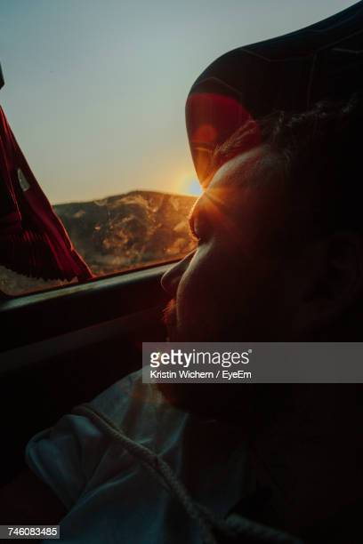 Back Lit Man Relaxing In Car During Sunset