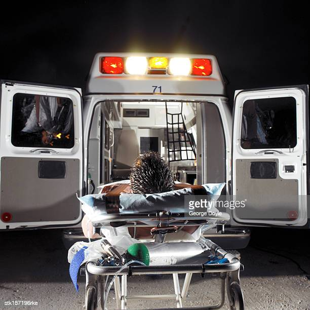 back of a patient lying on a gurney behind an ambulance
