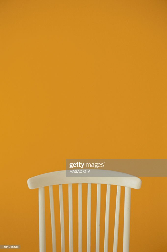 Back of a white chair against yellow wall