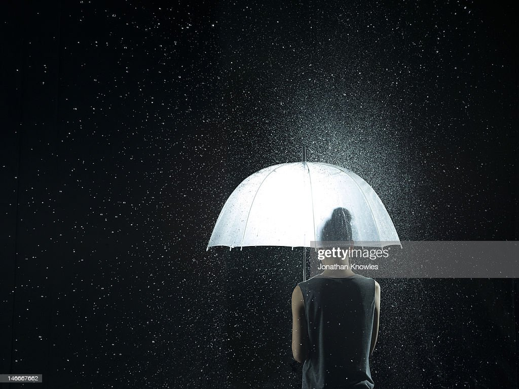 Back of a woman under a see-through umbrella