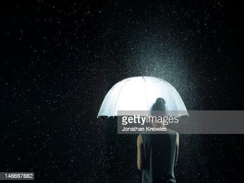 Back of a woman under a see-through umbrella : Stock Photo