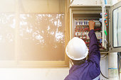 Back of asian engineer or technician in safety uniform and white security helmet turning on switch in the electrical cabinet with copy space and sun light effect for industrial concept