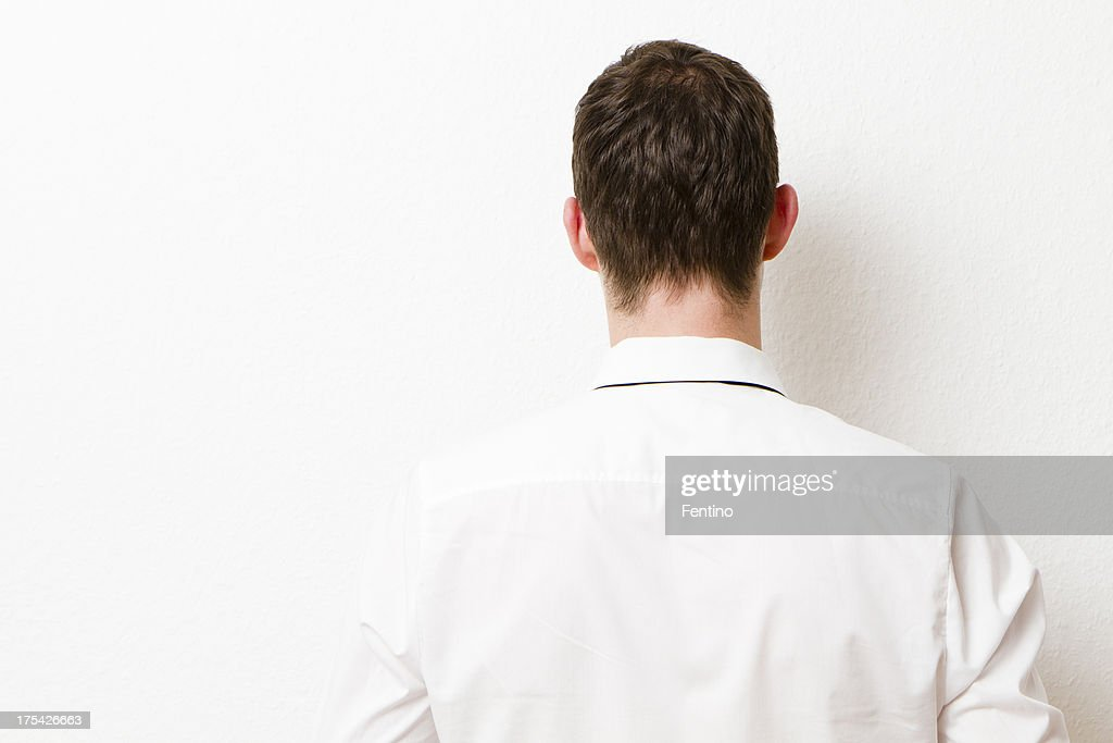 Back of Businessman against a Wall.