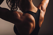 Close-up shot of back of female fitness model. Young woman in sports wear with muscular body.