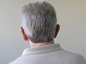 Back of head of a senior man against textured outside wall. Concept and idea, in denial and not facing problems, turning one's back on things.  Canon G9.