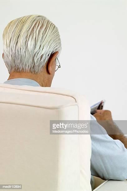 Back of senior man reading, close-up