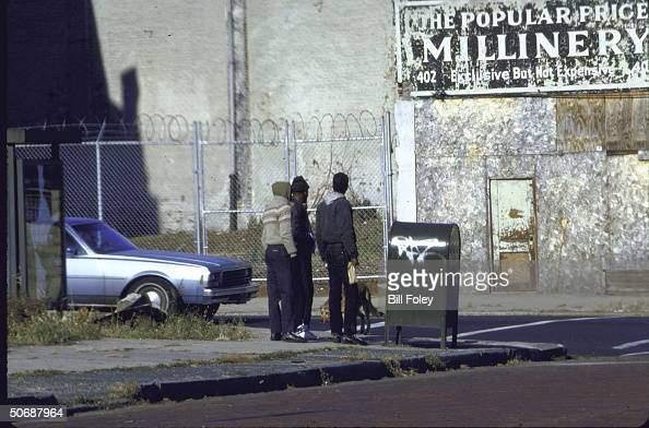 Back of three African American youths standing on a street corner beside a mailbox covered with graffiti across from a boarded dilapidated building
