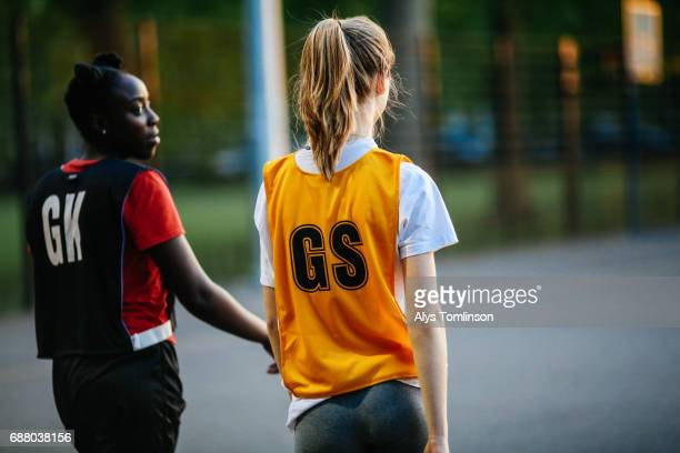 back of two netball players standing together on court