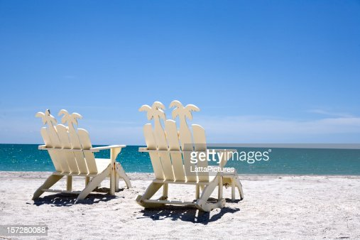 Back of two white wooden chairs on sand with ocean