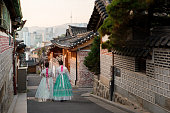 Back of two women wearing hanbok walking through the traditional style houses of Bukchon Hanok Village in Seoul, South Korea.