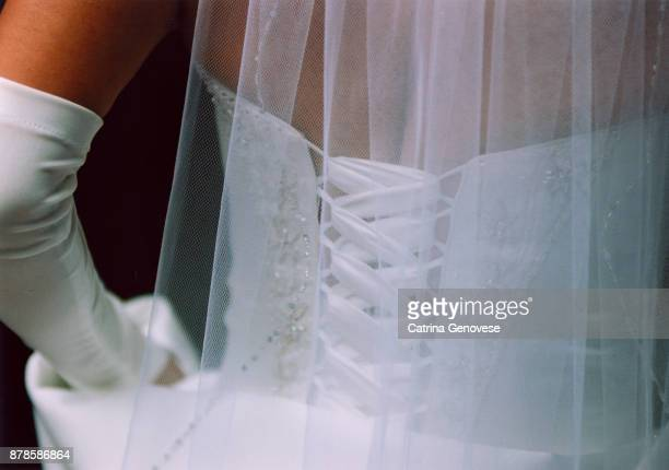 Back of white wedding dress and veil with white glove on wedding day