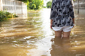 Woman wade flooding in her house. Closeup on her leg. View behind. Flooding at Loei province,  Thailand.