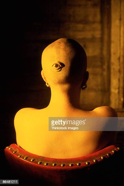 Back of woman's shaved head with eye