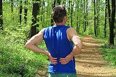 Back pain. Man Runner lower back pain injury