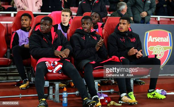 Back Row Chuba Akpom Ben Sheaf and Josh Dasilva of Arsenal Front Row Jordi OseiTutu Edward Nketiah and Marcus McGuane of Arsenal sit on the bench...