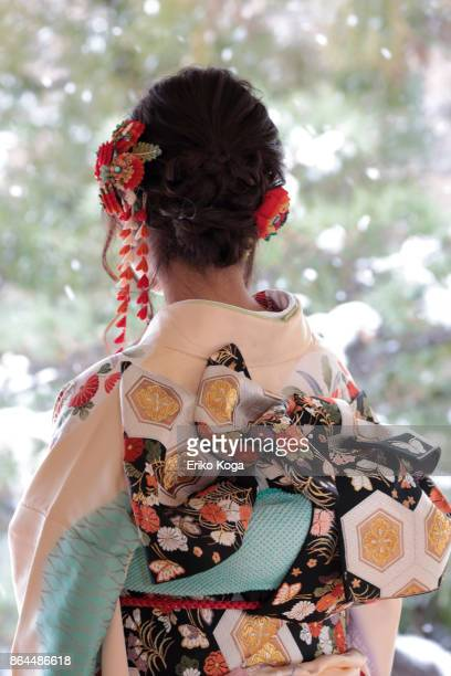 Back shot of young woman of coming‐of‐age ceremony in front of snowy Japanese garden