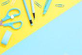 Blue school supplies on a yellow blue desk.
