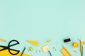 Creative, fashionable, minimal, school background with yellow supplies on cyan blue background. Back to school. Flat lay.