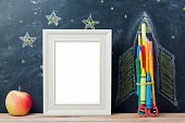 Back to school concept with rocket made from pencils, apple and poster mock up over chalkboard background