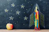 Back to school concept with rocket made from pencils and apple over chalkboard background