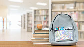 Back to school concept with school books, textbooks, backpack and stationery supplies on classroom desk with library or class background for educational new academic year begin or study term start
