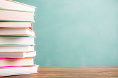 It's back to school time!  A large stack of textbooks to side makes frame composition.  The pile of objects lies on top of a wooden school desk with a green chalkboard in the background.  The blank bl