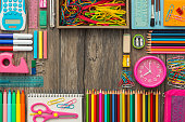 Back to school banner with colorful pencils and objects on a school desk, flat lay