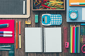 Colorful pencils and stationery on a school desk and open blank notebook, back to school concept, flat lay