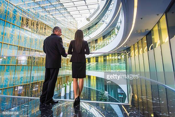 Back vieew of businessman and businesswoman in modern glass building
