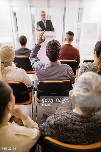 Back view of a businessman asking a question on seminar.