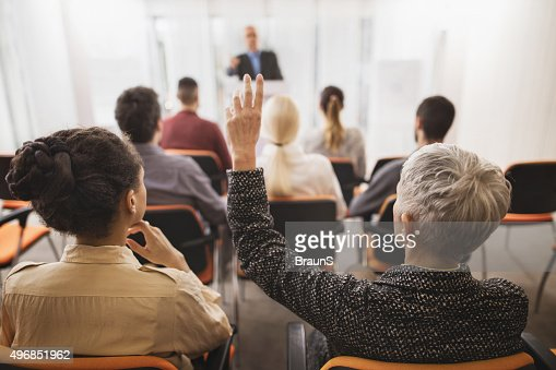 Back view of a businesswoman asking a question on seminar.