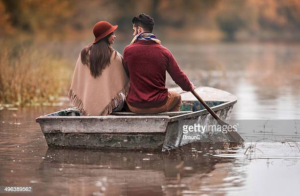 Back view of a couple paddling a boat in autumn.