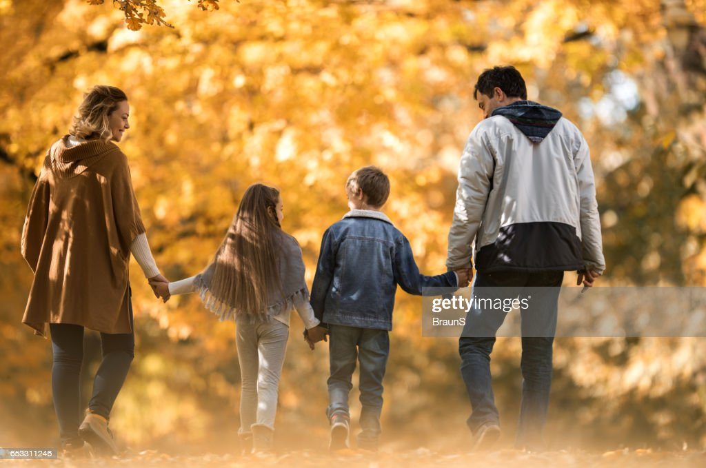 Back view of a family taking a walk in autumn. : Stock Photo