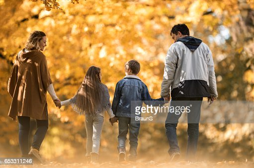 Back view of a family taking a walk in autumn. : Foto stock