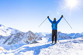 Back view of a happy skier with raised hands as a symbol of victory looking at a panoramic view of the snow white mountain landscape around