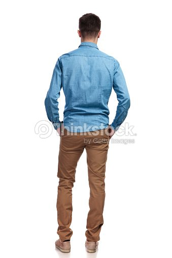 back view of a man standing with hands in pockets : Stock Photo